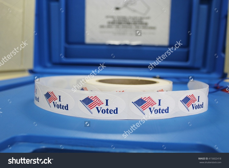 stock-photo-a-spool-of-red-white-and-blue-i-voted-stickers-with-american-flag-are-on-a-blue-voting-booth-415602418